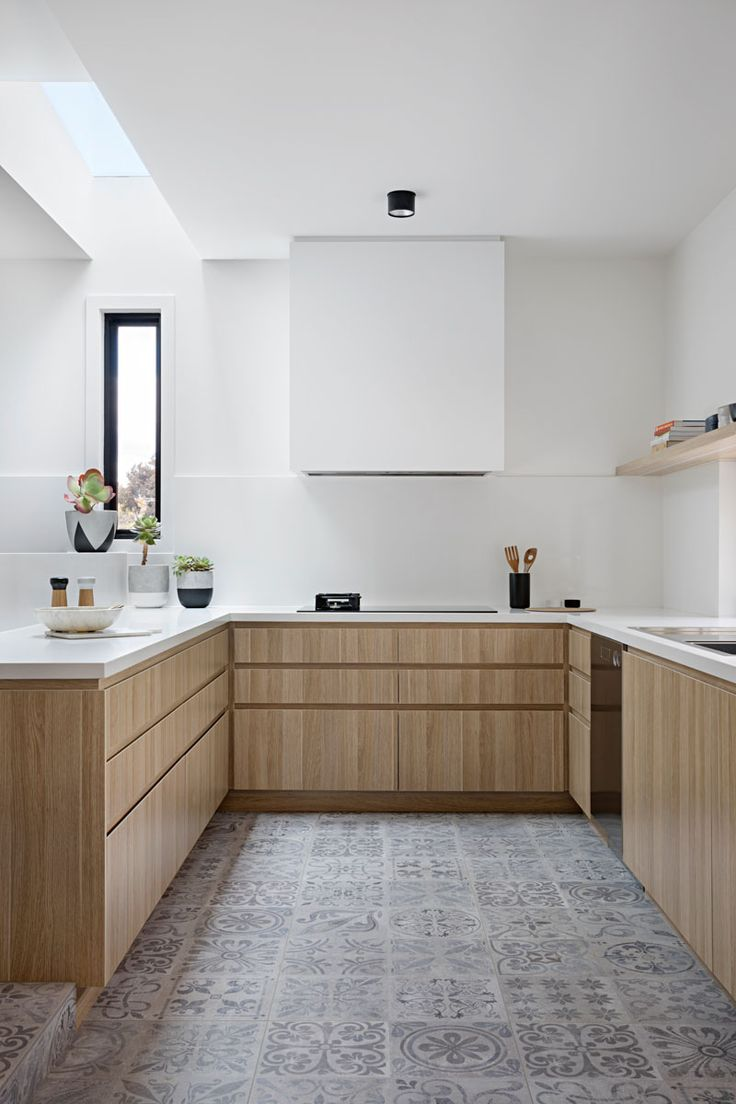 In this modern kitchen, there's a skylight above the white counters, and light wood cabinets help to keep the space bright. A light grey patterned floor tile adds some interest, while the exhaust fan above the oven is white so that it blends in with the wall.