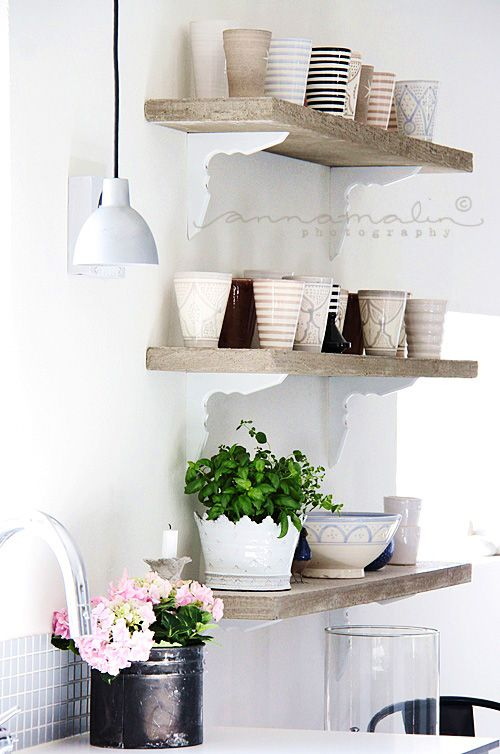 wood shelving with white walls + brackets white to match walls draws eye to wood shelves.
