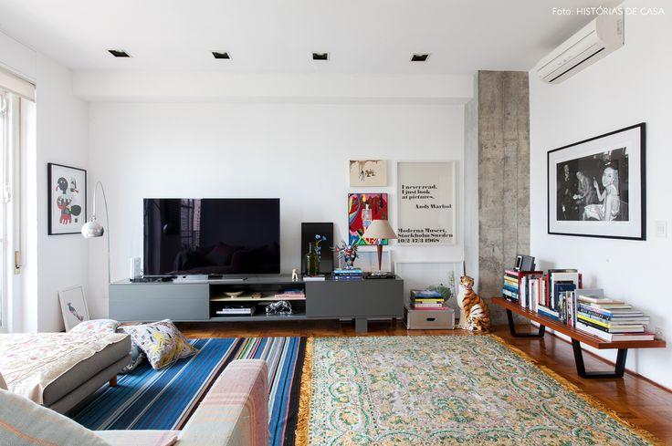 Nessa sala de estar, peças de design se misturam com móveis, acessórios e quadros coloridos.