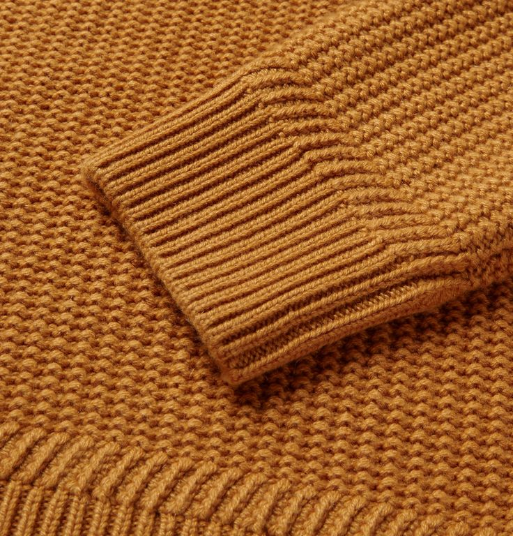 This cashmere Berluti sweater has been knitted with the textural 'seed' stitch, so named as it resembles scattered kernels. This effect is offset by a thickly ribbed shawl collar and cuffs. The vivid mustard shade makes a stylish point of difference to more muted tones. Shown here with a Brioni shirt, Berluti jeans and boots and a Bottega Veneta holdall.