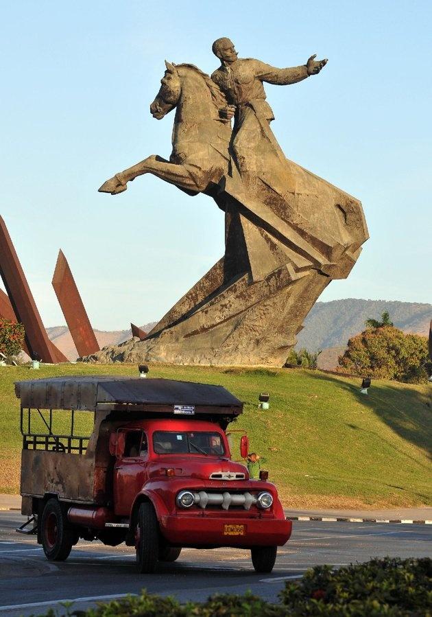 Un viejo camión usado para transporte de pasajeros circula cerca de la estatua del prócer de la independencia Antonio Maceo, en Santiago de Cuba