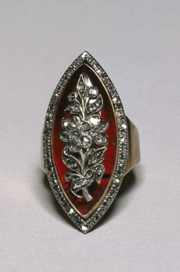 In the late 18th century and into the 19th century, marquise rings set with diamonds on dark blue or red enamel backgrounds became fashionable in Europe. The oval (marquise bezel), like this ring, and the rectangular (shuttle-shaped bezel) were the most popular shapes with diamonds set to imitate stars in the sky or floral sprays. It was charactersitic to frame these rings with a border of diamond sparks set in silver mounts.