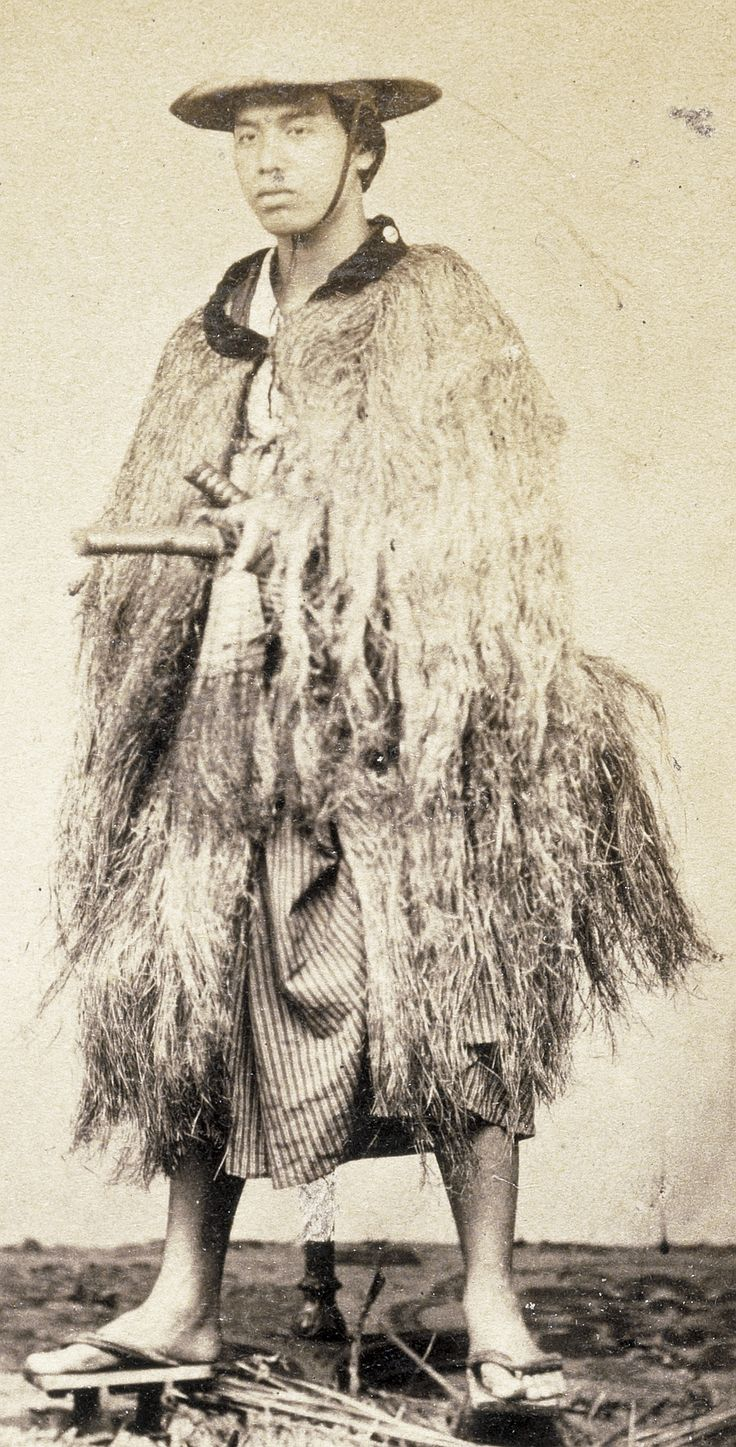 """Samurai, described as a """"yaconin"""", wearing a straw rain coat, photographed between 1867 and 1869."""