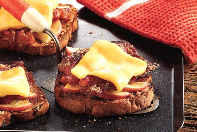 These cheesy open-faced sandwiches—featuring toasted raisin bread, bacon and sugared apples—are broiled until bubbly and served for breakfast.