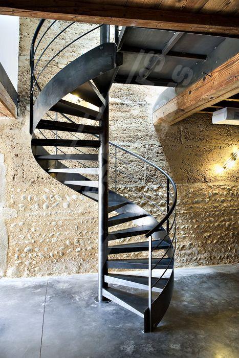 Photo S27 - SPIR'DÉCO® Contemporain Gamme Initiale Escaliers Décors®. Escalier d'intérieur métallique standard en colimaçon au design épuré et moderne pour une décoration contemporaine. La grande rigidité des escaliers d'Escaliers Décors® permet de gravir une grande hauteur ou plusieurs niveaux. Limon en tôle roulée formant ruban et soulignant les courbes de l'escalier hélicoïdal. Finition : acier brut patiné. - © Photo : Ludovic DI ORIO