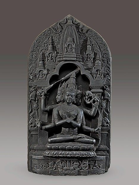 This sculpture represents an esoteric form of Manjushri, the Bodhisattva of Transcendent Wisdom. He has three heads and six arms; four hold a bow and arrow, a sword, and a lotus, while the remaining two hold vajras (thunderbolt scepters) and are crossed at the chest in an esoteric gesture (mudra) identifying supreme wisdom