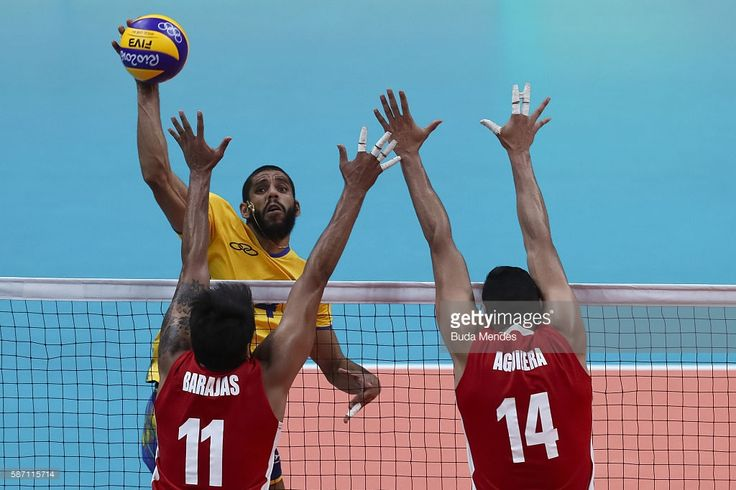 Wallace Leandro De Souza of Brazil (#4) spikes the ball against Jorge Barajas (#11) and Tomas Aguilera of Mexico during the men's qualifying volleyball match between Brazil and Mexico on August 7, 2016 in Rio de Janeiro, Brazil.
