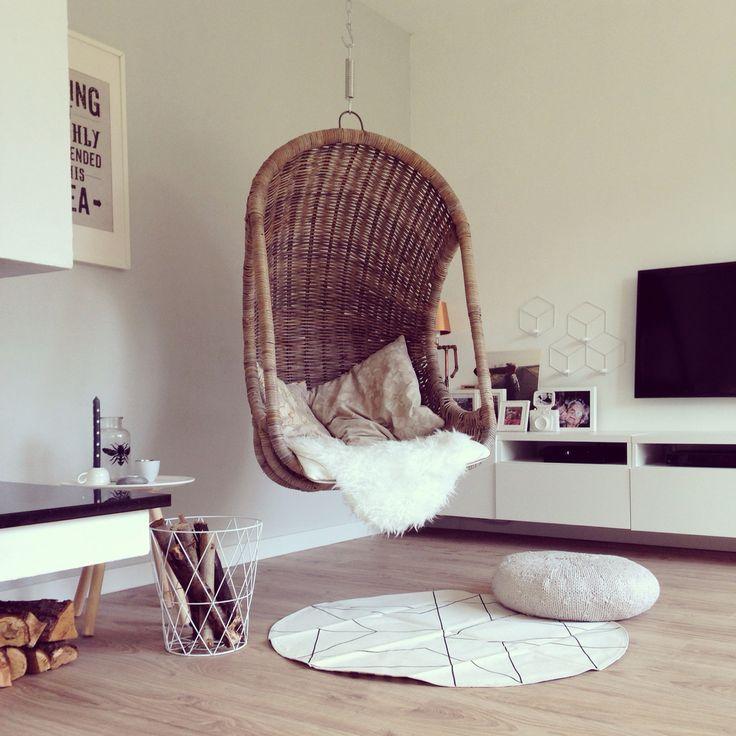 Hangstoel met vloerkleedje tussen de open haard en tv in.