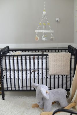 black crib with white polka dotted sheets - love this
