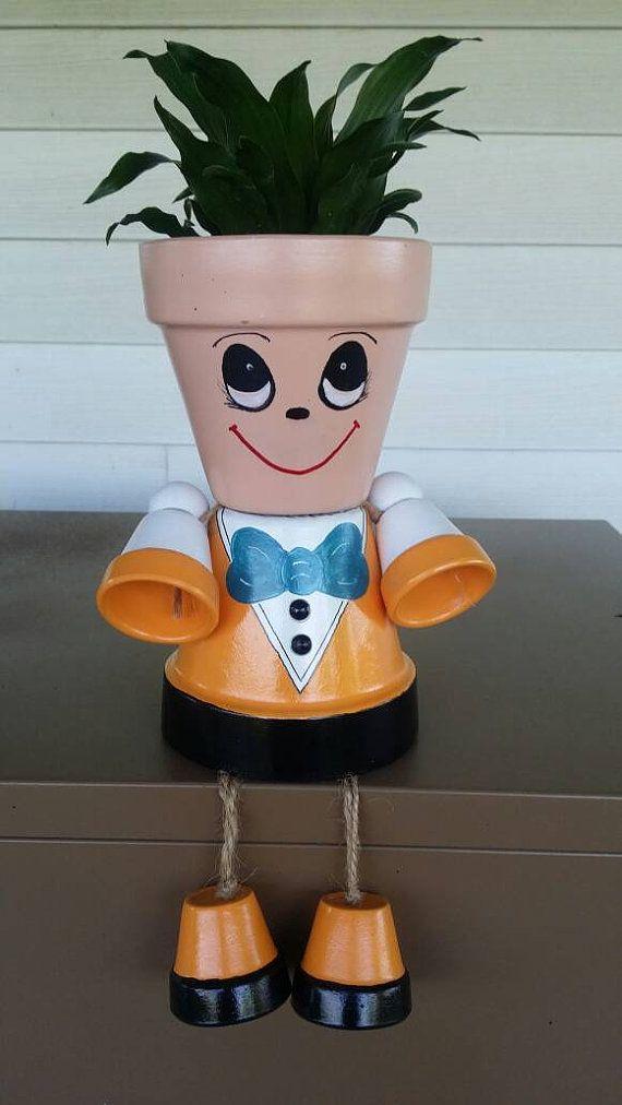Persona de pote del plantador, vestida con un traje naranja con moño