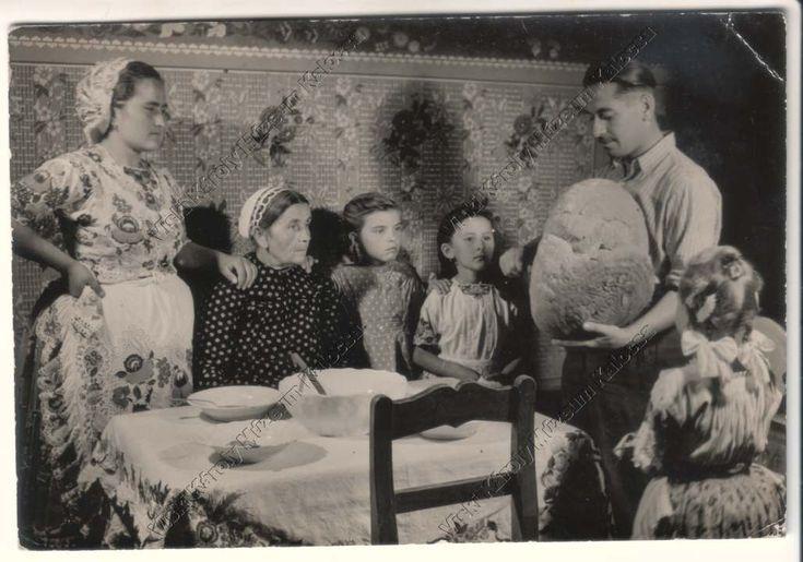 Kalocsai viseletbe öltözött család a megterített asztalnál várja, hogy a családfő megszegje a kenyeret.
