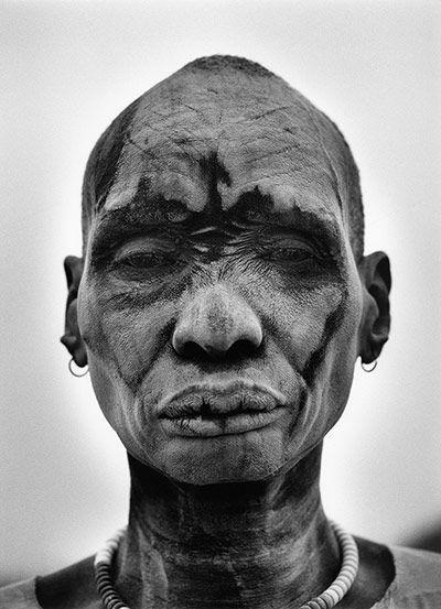 Sebastião Salgado em ação na África, fotografado por  seu filho, Juliano Salgado, e imagens de Gênesis: campo  de gado da tribo Dinka, sul do Sudão, e guerreiro Dinka com  a pele coberta de cinzas para proteção contra insetos e parasitas.