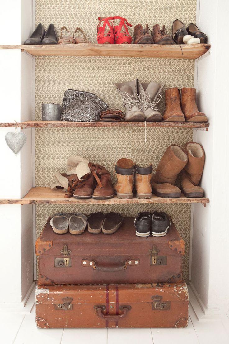schoenenrek met mooie houten planken in de nis naast de deur