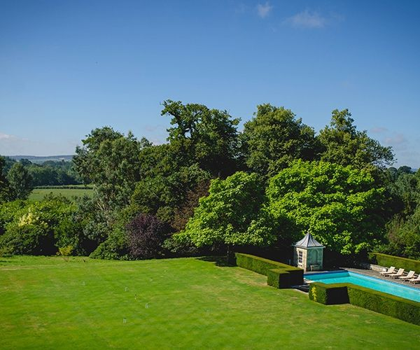 The lushious green lawn and outdoor swimming pool at Cowdray House wedding venue in West Sussex | CHWV
