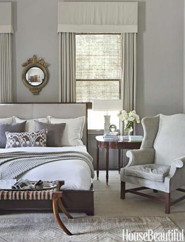 """drapery   To make the master bedroom of this Alabama house more dynamic, designer Betsy Brown chose bright white bedding and a white lampshade. """"A room of creams and beiges needs something stark and shiny white. You have to interject elements that add intense personality,"""" Brown says. Walls are Rockport Gray by Benjamin Moore. Saber Leg ottoman by Formations. Cashmere blanket from Suite Dreams."""