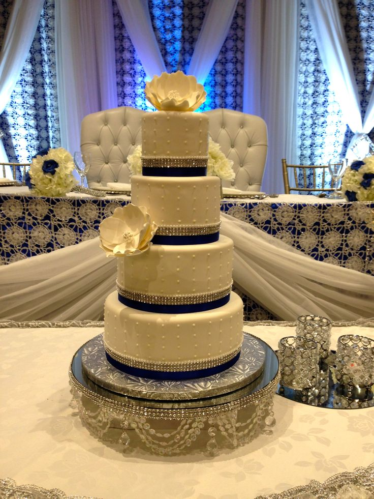 Royal blue accent on 4-tier wedding cake with  large magnolia flowers.