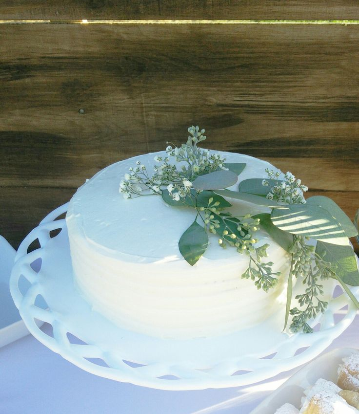 White with greenery neutral color baby shower cake. Baby