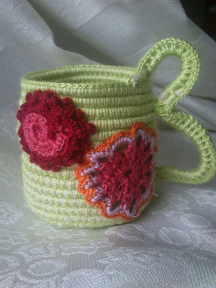 cesto con forma de jarra y motivos a crochet cosidos. Con asa doble