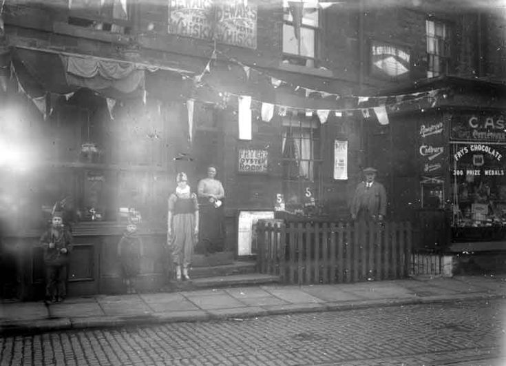 Street of shops, decorated with flags 1910 Dewsbury Yorkshire