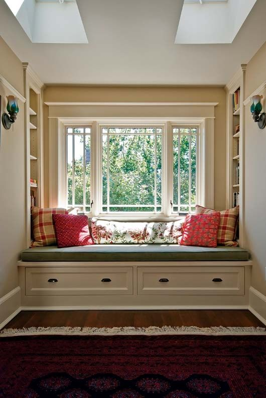 A built-in bench on the second floor is flanked by inset bookcases   sconces