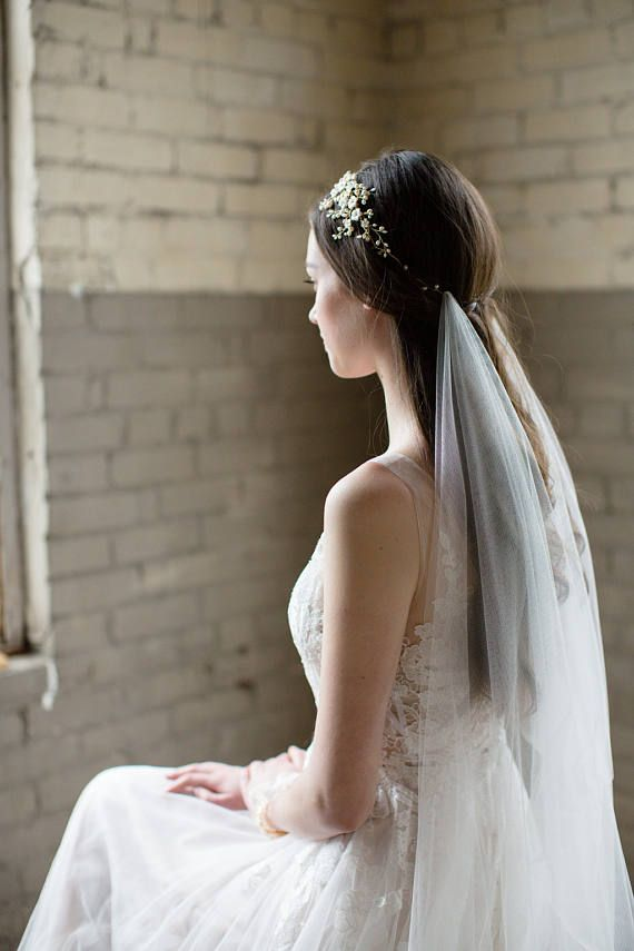 With an elegant drape and dramatic scooped back, the Jade draped veil is a perfect addition to a modern bohemian brides look. Handcrafted from the softest English net, this veil loves to shows off your flawless bridal hairstyle and the back of your gown. Wear this veil on its own for effortless glamour, or pair it with a bridal crown or comb for an ultra-chic look. Shown in Chapel length with our Ayame and Anastasie headpieces, sold separately. DETAILS – Hand-cut from soft and luxurious Engli…