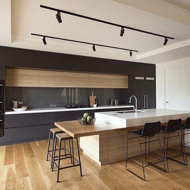 WEBSTA @ ohlaemcasablog - Cozinha super elegante ✨ Os armários e a torre quente em tom escuro enquadram a bancada e a faixa de armário amadeirados, constituindo um design super contemporâneo  A ilha (essa bancada solta, sabe?) se divide em duas alturas: a primeira adequada para sentar-se e comer e a segunda, para preparos de comida!  | Por Alta Architects #cozinhasohlaemcasa #integraçãoohlaemcasa