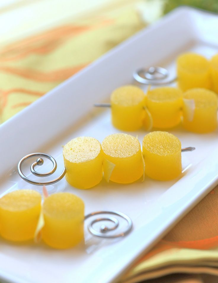 Mimosa Jelly Shots, cut with an oval cookie cutter and skewered with edible flower petal