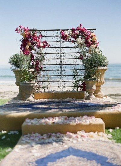 """30 Unique Altar Alternatives For Outdoor Weddings: Create your own """"outdoor chapel"""" with standing arches at the end of the aisle, then add a crystal chandelier to amp up the romance.  Source  : With large potted plants and gorgeous, sprawling flowers, a sculptural piece is transformed into a beautiful backdrop that's perfect for a romantic beach wedding.  Source"""