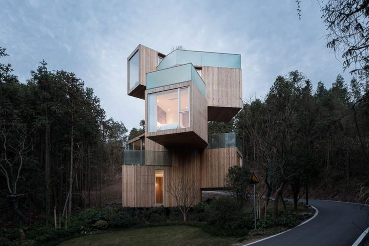 Timber-clad rooms are stacked vertically and rotated around a spiral staircase to form this hotel in China's Anhui province.