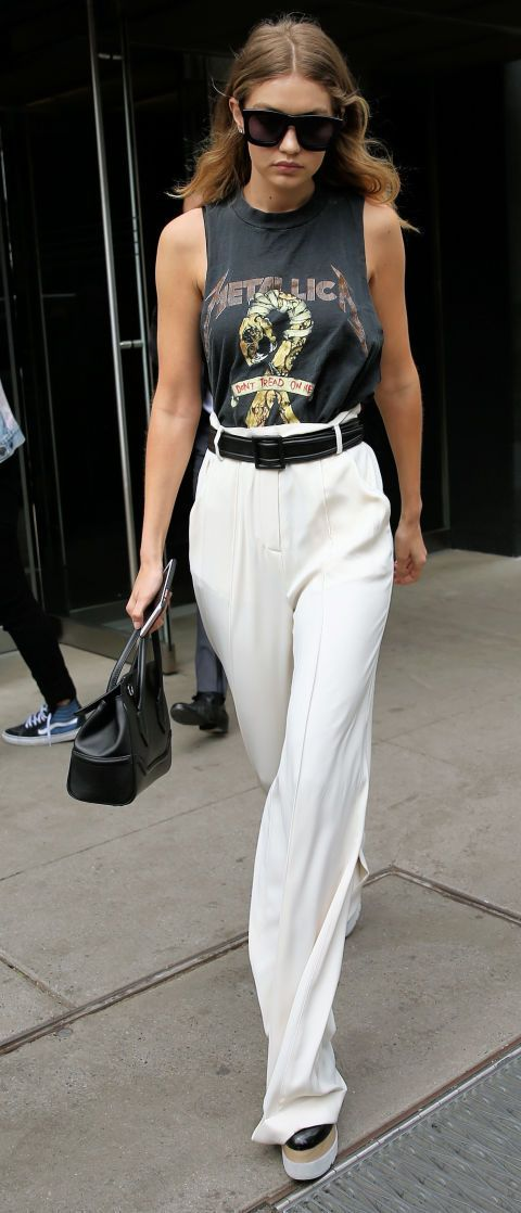 Gigi Hadid dresses up a Metallica band t-shirt with a pair of high-waisted cream pants. See all the model's best street style outfits here #Mylifemystyle