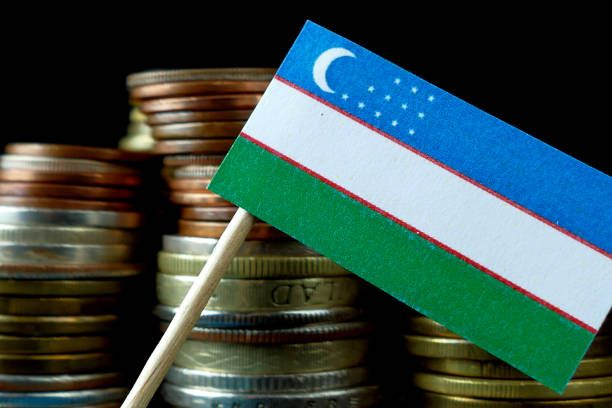 uzbekistan flag waving with stack of money coins macro