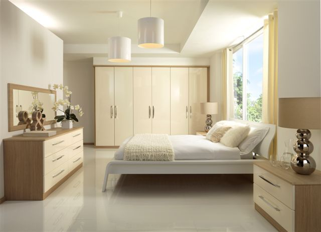 a firm favourite cream gloss fitted wardrobe run and low units on an aregon oak carcass. Black Bedroom Furniture Sets. Home Design Ideas