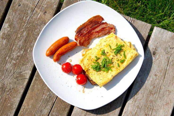Lækker og nem brunch tallerken med en luksus omelet, bacon, brunchpølser og grillede tomater. Klar på grillen på få minutter. Foto: Guffeliguf.dk.