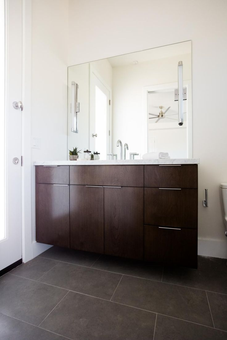 To add a touch of drama and depth to this otherwise white bathroom, Pure Design Interiors added a dark brown vanity and large brown floor tiles to complement the simple lines of the room. A large wall mirrors frames the entire vanity and slim, contemporary-styled cabinet pulls complete the look.