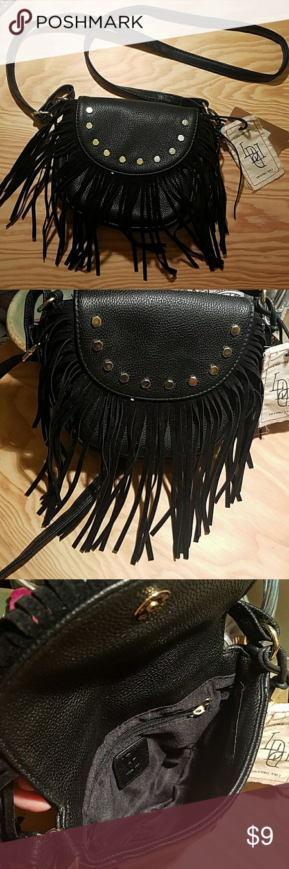 """Black Fringe Purse This perfect size purse is great for a night out, a concert, the fair or a festival. Faux leather with suede fringe this one pocket cross body bag will become your best friend! Accented with gold studs this brand new bag is ready to ship Dimensions: about 6"""" W x  5"""" high x 2"""" deep Magnetic button closure, one small zippered pocket inside the purse Like Dreams Bags Mini Bags"""