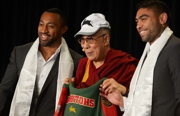 Tibet's exiled spiritual leader the Dalai Lama (C) holds a South Sydney Rabbitohs rugby league team jersey and wears a club cap as he poses alongside players Nathan Merritt (R) and Roy Asotasi (L) following a presentation during a press conference in Sydney on June 13, 2013. The Dalai Lama is on a national tour to Australia for ten days with events throughout the visit carrying the message 'Beyond Religion; Ethics for a Whole World'.