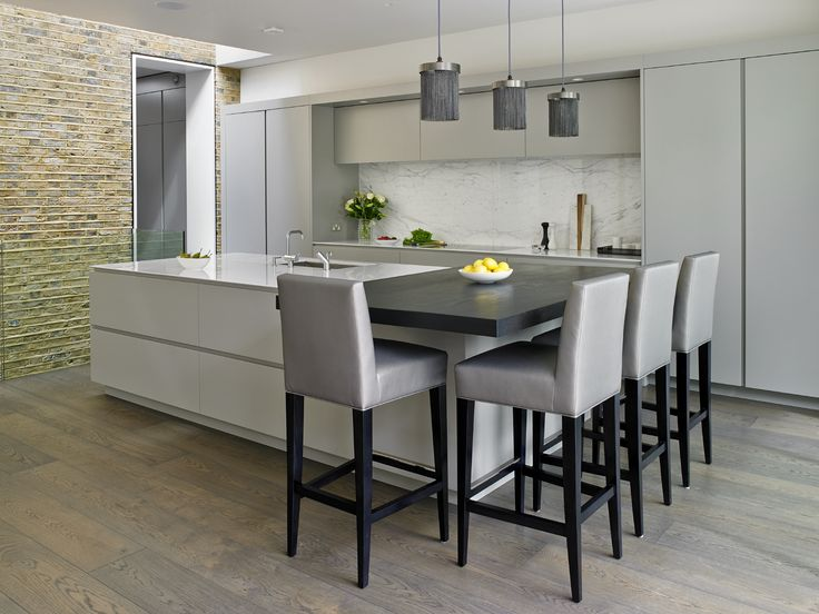 Grey Handleless kitchen design by Brayer. Victorian house renovation with secret cloakroom, large island and hidden breakfast cupboard. Silver grey matt lacquered cabinets with pure white composite work surfaces.