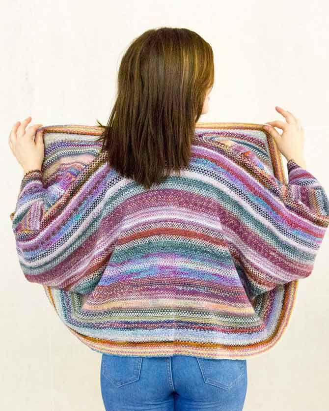 Friendship Blanket Shrug designed by Jacqueline Grice for Spring 2016 Issue. I believe the Friendship Blanket Shrug is the perfect name for this knit project. It was born from left over sock yarn I had in my stash and the very many bits and pieces of left over sock yarns received from friends over a span of time. I started to knit a scarf at first, but the yarn just kept coming, so it evolved into a lap size blanket. I kept on knitting still receiving left over yarns from friends,