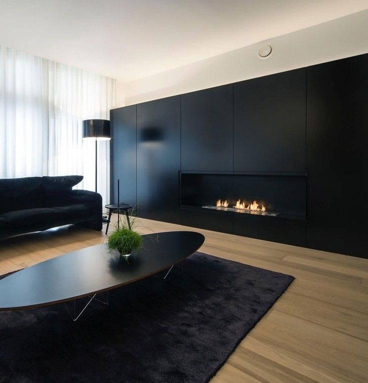 The focal wall in this minimal small living room incorporates a hidden fireplace and matches the red and black colour scheme of the rest of the décor in the space.