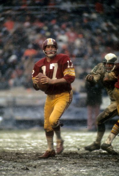 Quarterback Billy Kilmer of the Redskins gets ready to pass against the Eagles.  Love this picture!  Reminds of the days when football was football and mud was mud!