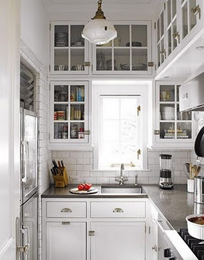 Glass cupboard doors draw the eye into the shelves, leading the mind to the actual wall, instead of the cabinet door, increasing room size. Surrounding cabinets also serve to reflect/direct light from the window.