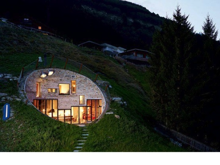 Stone faced concave earth house night buildings for Stone faced houses