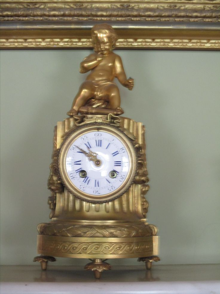 French gilt metal clock with enamelled dial surmounted by a figure of Cupid.  Circa. 19th century.