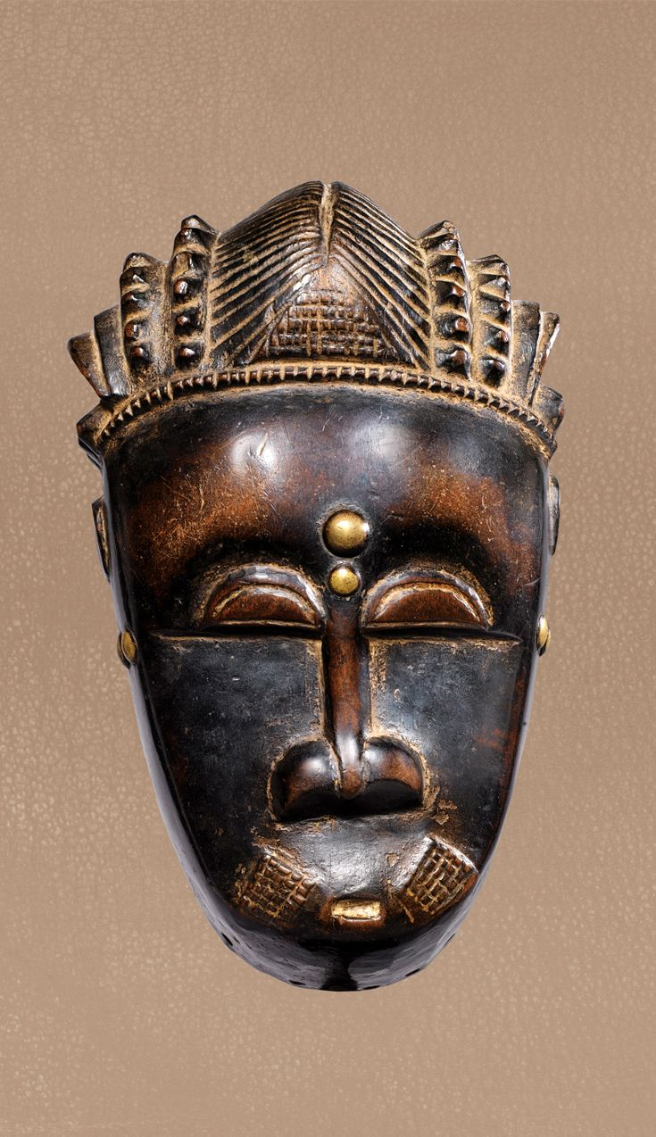 Africa | 'Mblo' mask from the Baule people of the Ivory Coast | Wood and metal nails