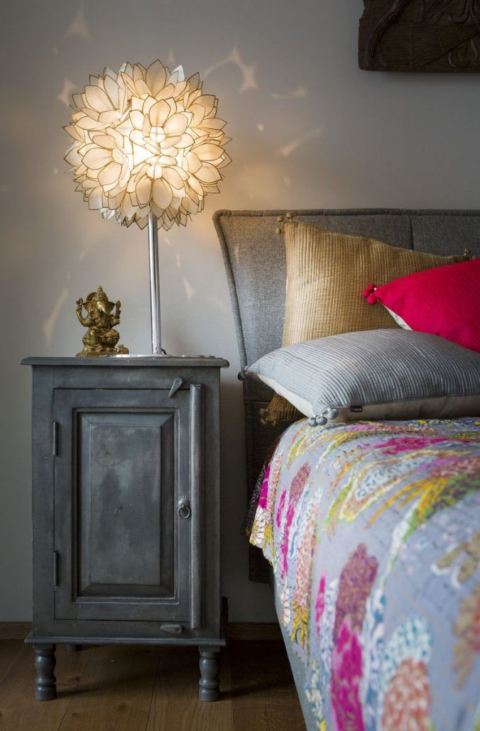 Mother of pearl standing light combined with a metal sidetable and indian antique statue. Bed accesorized with Vivaraise pink,gold and pink pillows and matching bed cover. #bedroom #interior #design #french #women #romantic