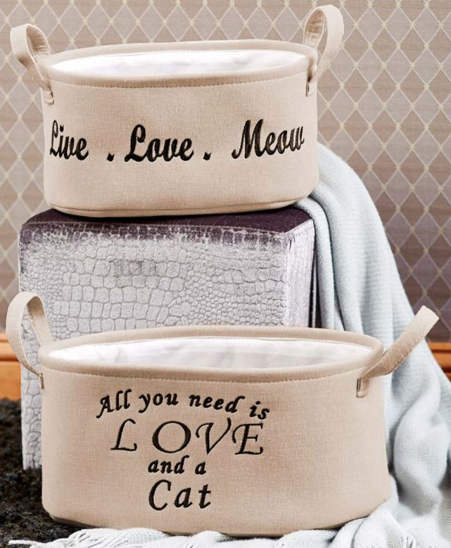 "Use these pet storage bins for toys, supplies and more! This set includes 2 bins in different sizes. The small bin is embroidered with the sentiment ""Live. Meow"". The larger bin is embroidered with the sentiment ""All you need is love and a cat"". 