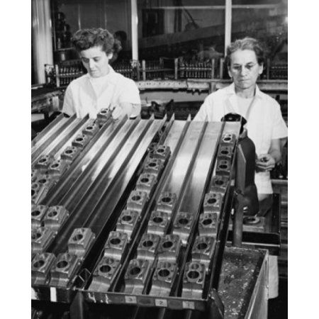 Two female workers using air gauge to sort cylinders used in a household refrigerator compressor Canvas Art - (24 x 36)