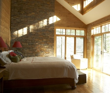 Dramatic stone feature wall natural materials dominate this cottage bedroom