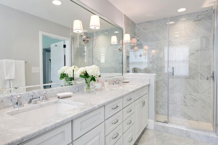 Light gray marble throughout this transitional bathroom creates a peaceful, spa-like vibe. A beautiful white vanity features a large mirror with mounted sconces and plenty of drawer space to keep the counters clutter-free.