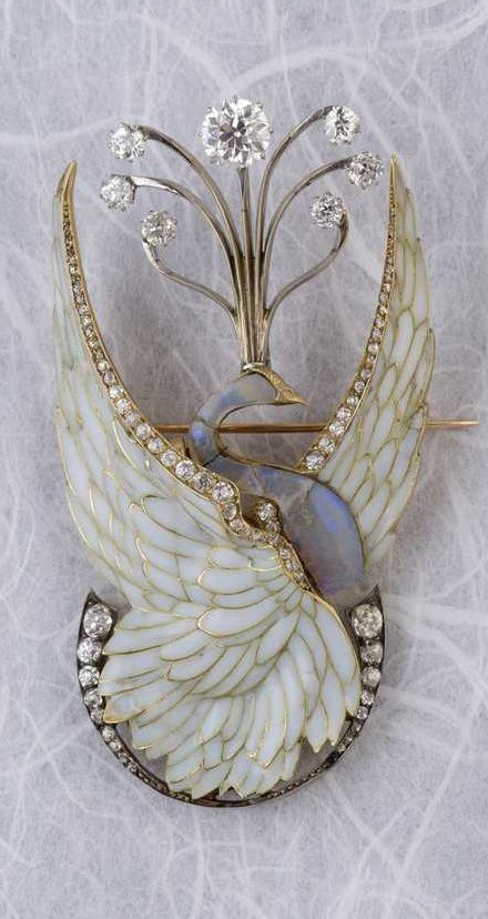 """Philippe Wolfers - A rare Art Nouveau gold, silver, plique-à-jour enamel, diamond and opal brooch, with later alterations. Designed as a swan with its wings spread, the body in opal. Probably altered in 1950 with the addition of diamonds surmounting the swan's head and the crescent moon. Signed PW on reverse and inscribed """"Ex. Unique"""""""